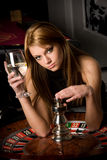 Jonge vrouw in casino met een glas van drank Royalty-vrije Stock Afbeelding