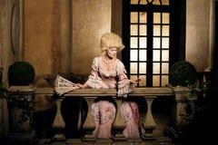 Jonge vrouw in de 18de eeuwbeeld het stellen in uitstekende buitenkant Stock Foto