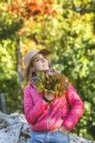 Jonge vrouw in de herfstpark met esdoornblad stock foto