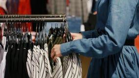 Jonge vrouw in de klerenwinkel stock videobeelden