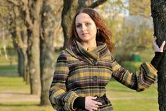 Jonge vrouw in de lentepark met nadenkende glimlach Royalty-vrije Stock Afbeeldingen