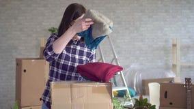 Jonge vrouw in de uitpakkende dozen die van het plaidoverhemd zich aan nieuw huis bewegen stock video