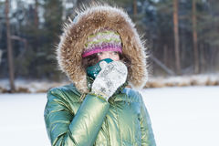 Jonge vrouw in de winterbos tijdens koud weer die haar gezicht in sjaal in openlucht verbergen Stock Afbeeldingen