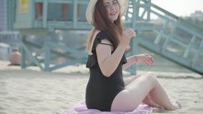 Jonge vrouw in de witte hoed die zonbad op het strand nemen Het meisje die en camera draaien bekijken De vrije tijd van de zomer stock footage