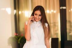 Jonge vrouw in de witte telefoon en de glimlach van het overhemdsgebruik Gelukkig attrective meisje stock fotografie
