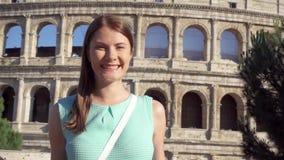 Jonge vrouw dichtbij beroemde aantrekkelijkheid Colosseum in Rome, Italië Vrouwelijke toerist die in langzame motie glimlachen stock footage