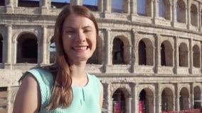 Jonge vrouw dichtbij beroemde aantrekkelijkheid Colosseum in Rome, Italië Vrouwelijke toerist die in langzame motie glimlachen stock videobeelden