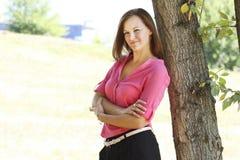 Jonge vrouw dichtbij bomen Royalty-vrije Stock Foto's