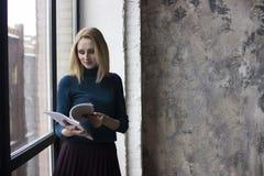 Jonge vrouw dichtbij het venster royalty-vrije stock afbeeldingen