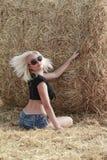 Jonge vrouw dichtbij hooibergen Stock Afbeeldingen