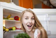 Jonge vrouw dichtbij koelkast thuis Royalty-vrije Stock Foto's