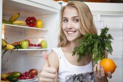 Jonge vrouw dichtbij koelkast thuis Royalty-vrije Stock Foto