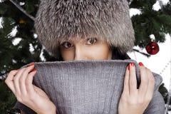Jonge vrouw dichtbij nieuwe jaarboom die warme hoed dragen Royalty-vrije Stock Afbeeldingen