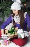 Jonge vrouw dichtbij nieuwe jaarboom met heden Royalty-vrije Stock Afbeelding
