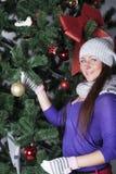 Jonge vrouw dichtbij nieuwe jaarboom met heden Royalty-vrije Stock Foto's