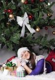 Jonge vrouw dichtbij nieuwe jaarboom met heden Stock Foto
