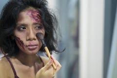 Jonge vrouw die één of andere speciale gevolgenmake-up op gezicht zetten stock fotografie