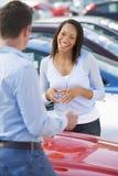 Jonge vrouw die aan autoverkoper spreekt Royalty-vrije Stock Afbeeldingen