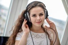 Jonge vrouw die aan de muziek op hoofdtelefoons luisteren Royalty-vrije Stock Afbeelding
