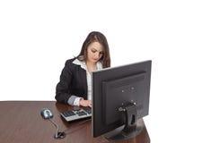 Jonge vrouw die aan een computer werkt stock afbeeldingen