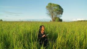 Jonge vrouw die aan een tablet in het park werken, zit zij op een groen gras algemeen plan stock videobeelden