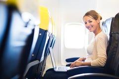 Jonge vrouw die aan haar laptop aan boord van een vliegtuig werken Royalty-vrije Stock Fotografie