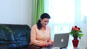 Jonge vrouw die aan haar laptop computer werkt stock footage
