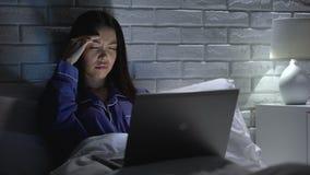 Jonge vrouw die aan hoofdpijn lijden, die in slaapkamer laat bij nacht, werkverslaafde werken stock videobeelden