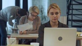 Jonge vrouw die aan laptop in het moderne bureau werken stock video