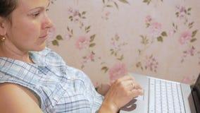 Jonge vrouw die aan laptop thuis op laag werken Aandachtig persen op touchpad stock videobeelden