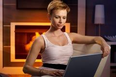Jonge vrouw die aan laptop thuis werken Stock Afbeeldingen