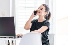 Jonge vrouw die aan laptop werken en door mobiele telefoon in heldere flats spreken royalty-vrije stock afbeelding