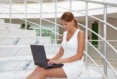 Jonge vrouw die aan laptop werkt stock fotografie