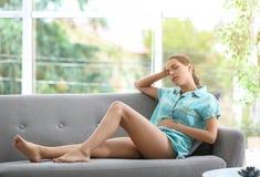 Jonge vrouw die aan menstruele klemmen lijden stock foto's