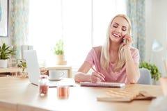 Jonge vrouw die, aan mobiel thuis werken die spreken stock foto's