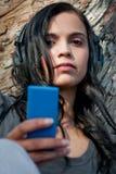 Jonge vrouw die aan muziek bij een park luistert Royalty-vrije Stock Afbeeldingen
