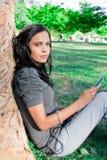 Jonge vrouw die aan muziek bij een park luistert Royalty-vrije Stock Foto