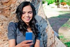 Jonge vrouw die aan muziek bij een park luistert Royalty-vrije Stock Fotografie