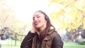 Jonge vrouw die aan muziek bij hoofdtelefoons en het dansen luisteren stock videobeelden