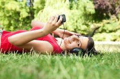 Jonge vrouw die aan muziek luistert stock afbeeldingen