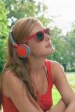 Jonge vrouw die aan muziek luistert Stock Afbeelding