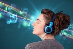 Jonge vrouw die aan muziek met hoofdtelefoons luisteren Royalty-vrije Stock Afbeeldingen