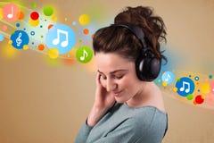 Jonge vrouw die aan muziek met hoofdtelefoons luistert Royalty-vrije Stock Foto's