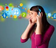 Jonge vrouw die aan muziek met hoofdtelefoons luistert stock afbeeldingen
