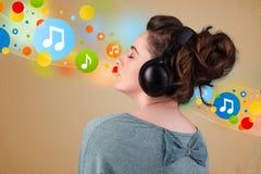 Jonge vrouw die aan muziek met hoofdtelefoons luistert Stock Fotografie