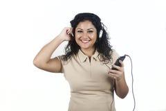 Jonge vrouw die aan muziek met mobiel luisteren Royalty-vrije Stock Foto