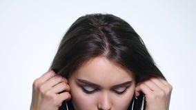 Jonge vrouw die aan muziek met oortelefoons luisteren die op witte achtergrond wordt geïsoleerd stock footage