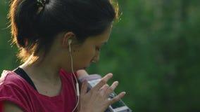 Jonge vrouw die aan muziek met oortelefoons op slimme telefoon app voor geschiktheidsmotivatie luisteren Atletenagent in sportkle stock videobeelden