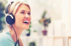 Jonge vrouw die aan muziek op hoofdtelefoons luisteren Stock Foto's