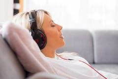 Jonge vrouw die aan muziek op hoofdtelefoons thuis luisteren Stock Foto